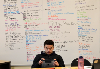 student sitting and reading a tablet in front of a whiteboard